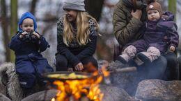 Tre børn hygger ved bål i naturen.