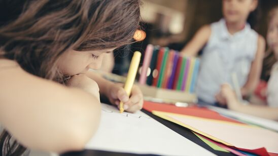 Barn tegner eller skriver liggende ind over bordet