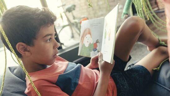"""Barn læser i Herlev Biblioteks """"skov"""" af grønne reb"""