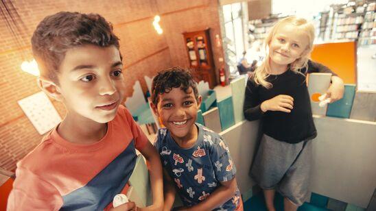 Tre børn i toppen af Herlev Biblioteks legetræ