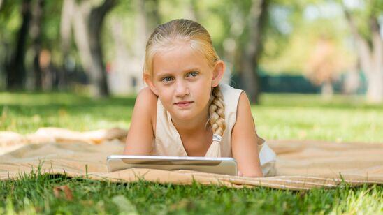 Du kan lære om naturen online - men også tage din viden med ud, som dette barn i en park med sin tablet.