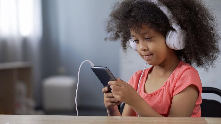 Barn med høretelefoner på ørerne og smartphone i hånden