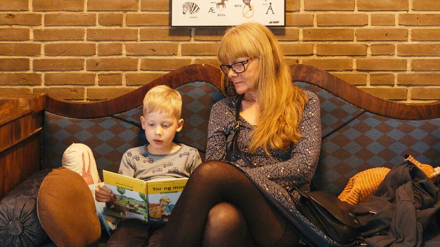 Barn og voksen læser i sofa