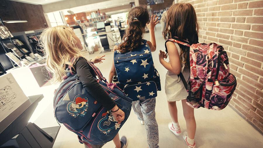 Tre børn med skoletasker på
