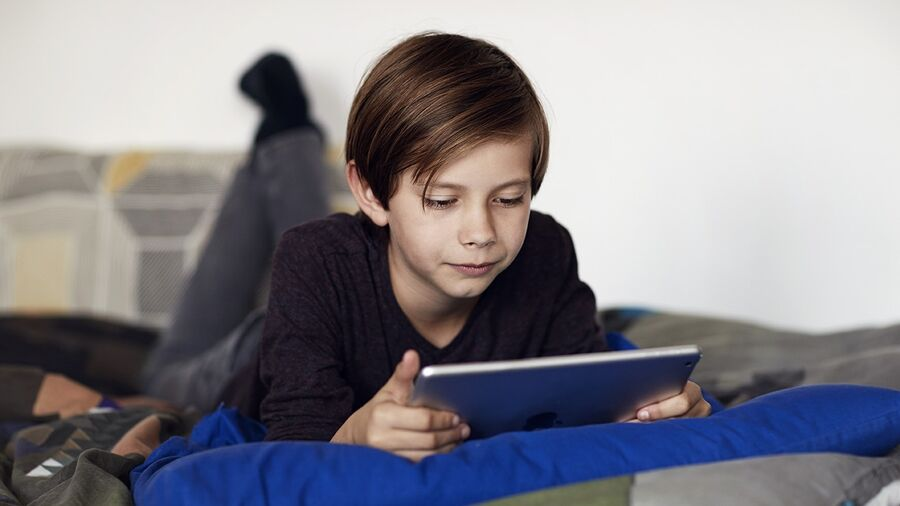 Barn læser på tablet. Foto: eReolen