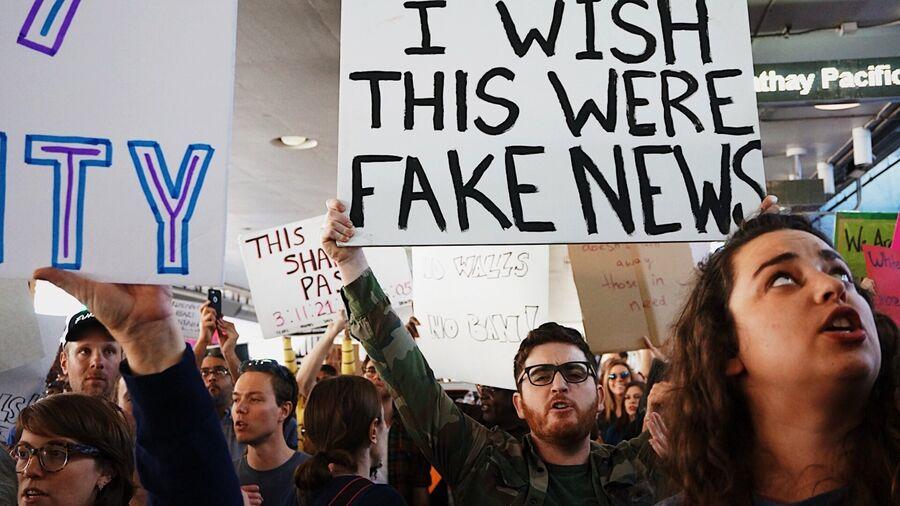 "Mennesker i demonstration, skilt med teksten ""I wish this were fake news"""