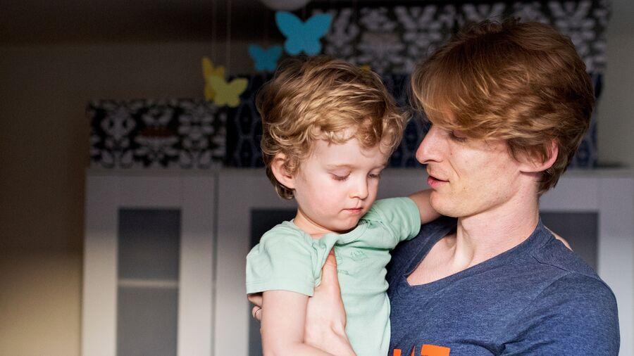 Far med barn på tre-fire år på armen. Barnet ser lidt tænksom eller trist ud.