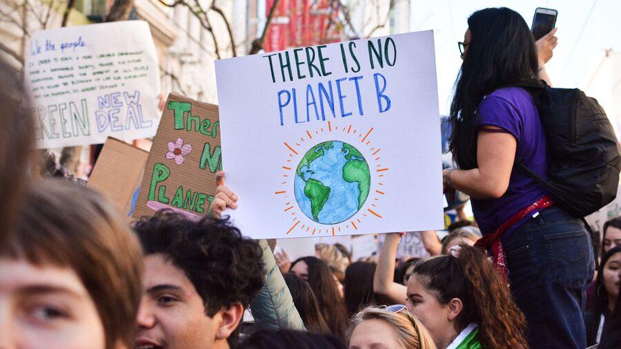 """Mennesker til klima-demonstration, skilt med teksten """"There is no planet b"""""""