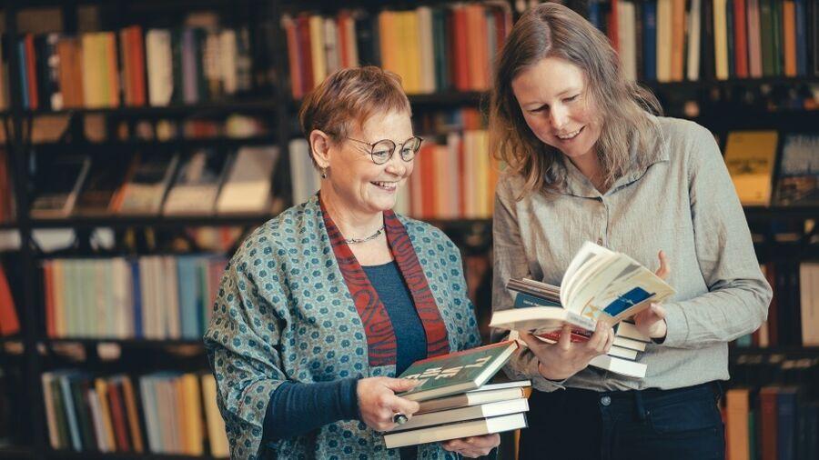 To af bibliotekets ansatte, Marit og Nanna, med bøger i hænderne og smil på læben foran en af bibliotekets reoler.