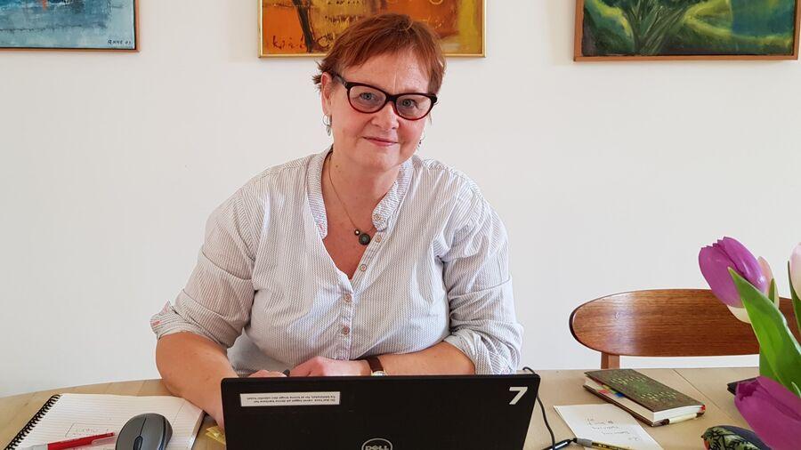 Bibliotekar Marit Juhl ved bærbar computer på spisebord. Farverige malerier i baggrunden, tulipaner i forgrunden.