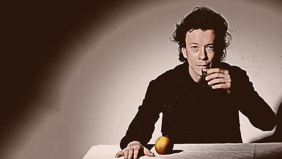 Musiker Peter Rosendal ved bord med æble på og glas i hånden