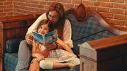 Barn får læst bog højt i sofa