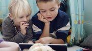 To børn kigger sammen på en tablet.