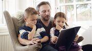 Far læser højt for to børn i lænestol