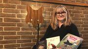 Bibliotekar Hanne Svendsen Holme med favnen fuld af børnebøger